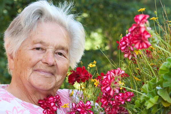 Older woman standing next to dark pink flowers.