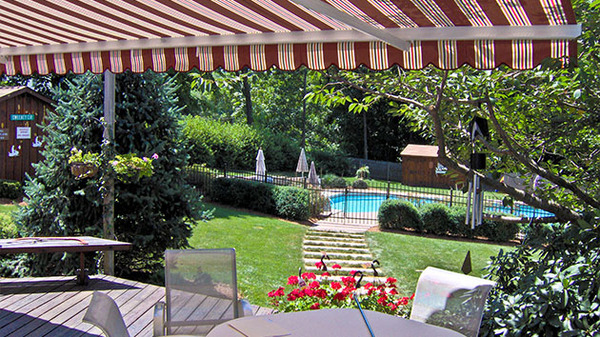 Backyard with pool, deck and awning.