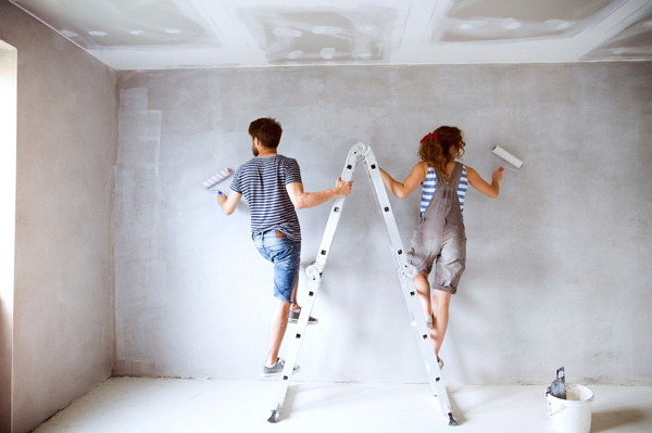 Couple on a ladder painting a wall.