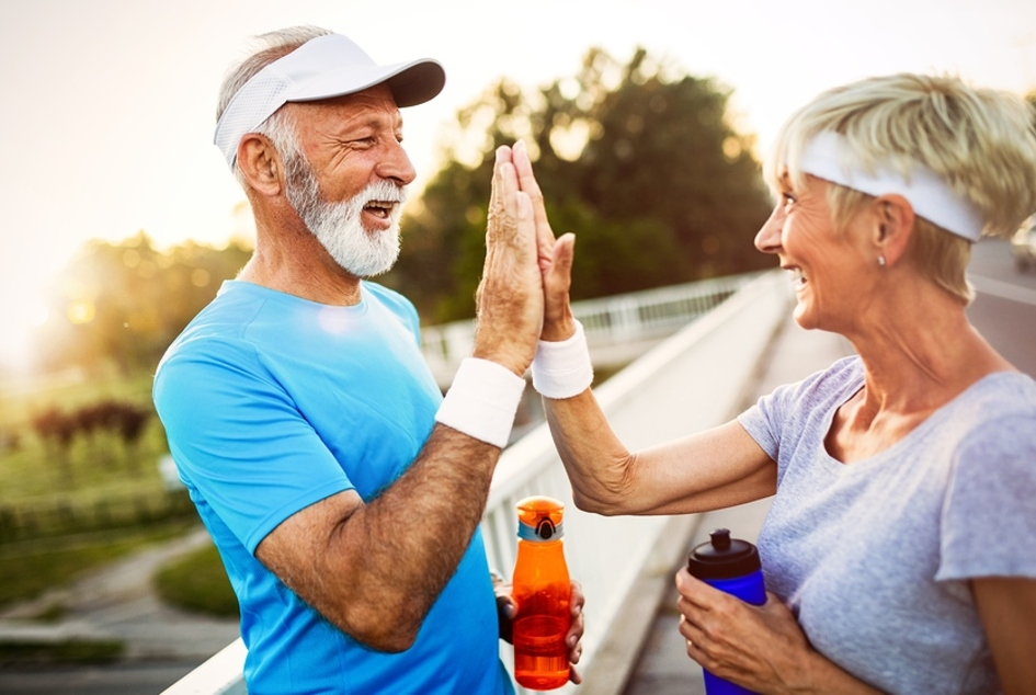 Two older people giving a high-five with workout clothes on.