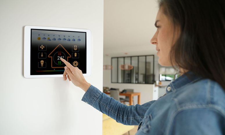 Woman checking her home digital thermostat.