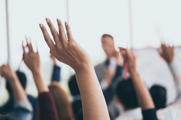 Group of people raising their hands at a seminar.