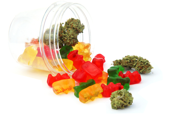 Cannabis candies and buds in a glass jar.