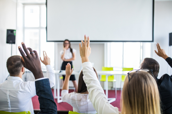 Conference room filled with people raising their hands.