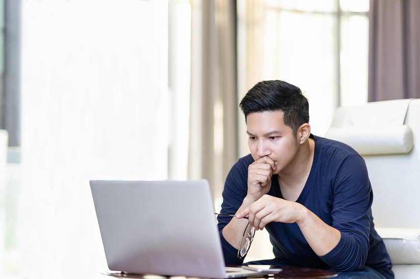 Man in front of a laptop appearing undecided