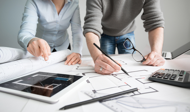 Two people drawing floor plans referencing a table app and calculator.