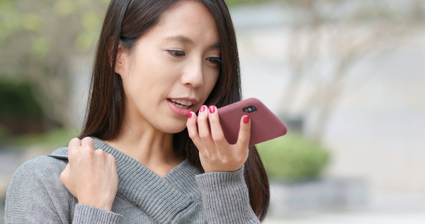 Giving a voice command to a phone.