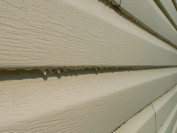 Tan colored vinyl siding with drops of water at the bottom.