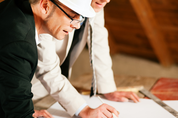 Two men with hard hats looking at plans.