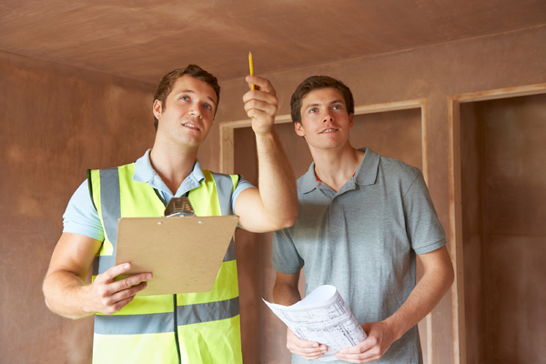 Two men looking at a ceiling with a clipboard and pencil.