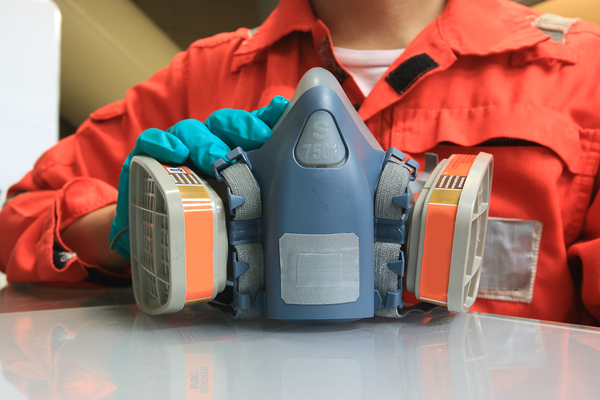 Person in an orange work suit holding a respirator.