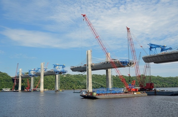 Construction of bridge over water with barges and cranes.