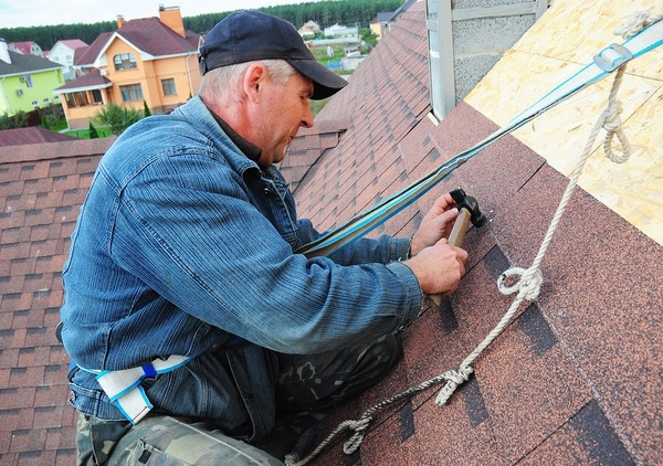 Man working on a roof with a safety strap around his waist.