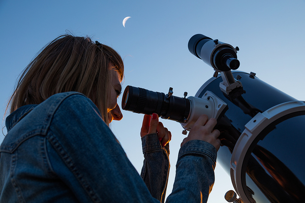 Woman looking into a telescope.