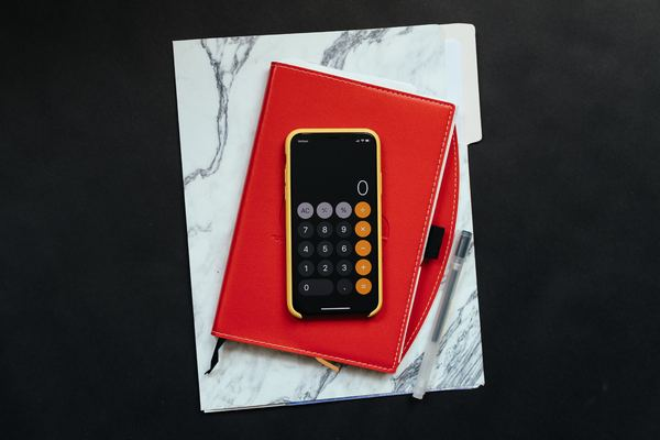 Phone with the calculator app on display on top of a red notebook.