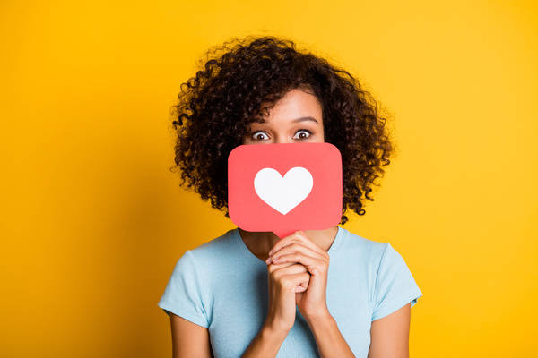 Holding a heart emoji.