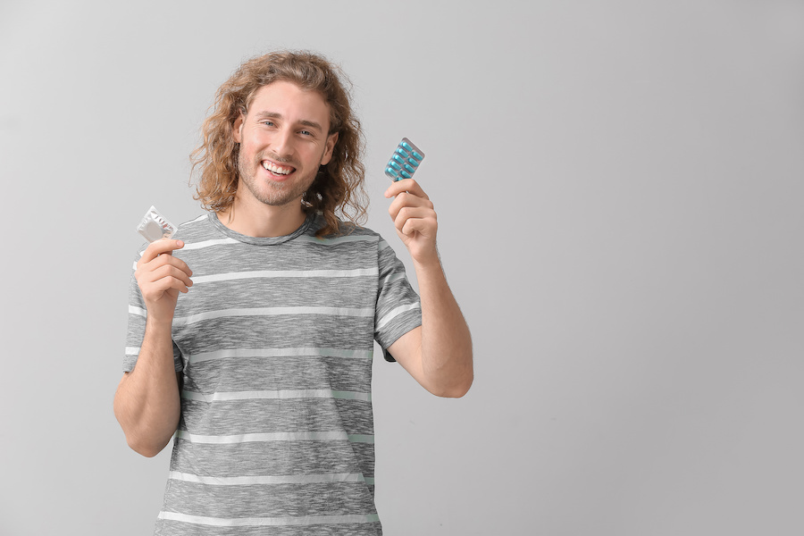 Holding a a blue pill packet and condom.