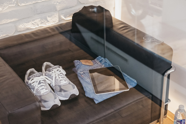 Clothing and a tablet on a chair.