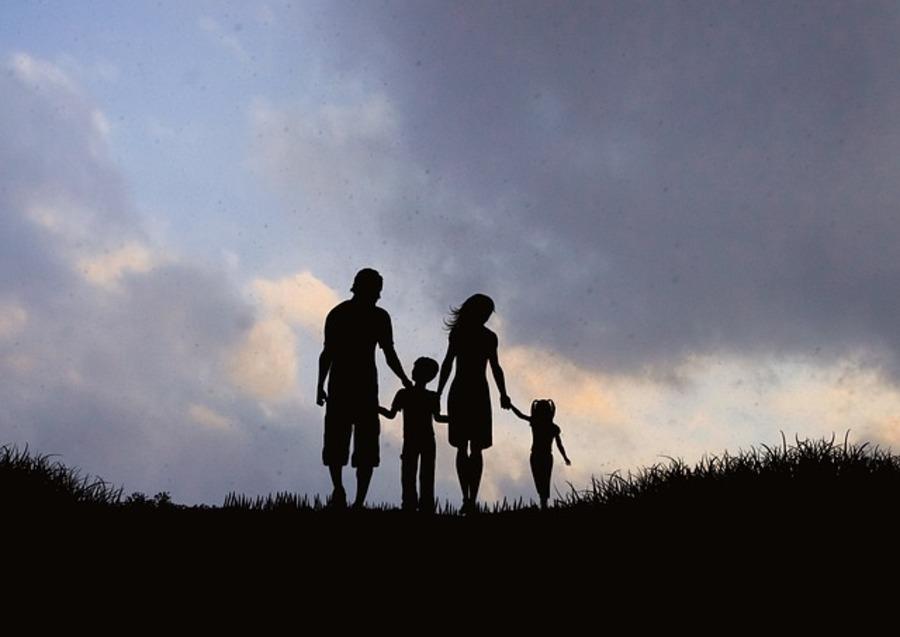 Family of four walking in a field.