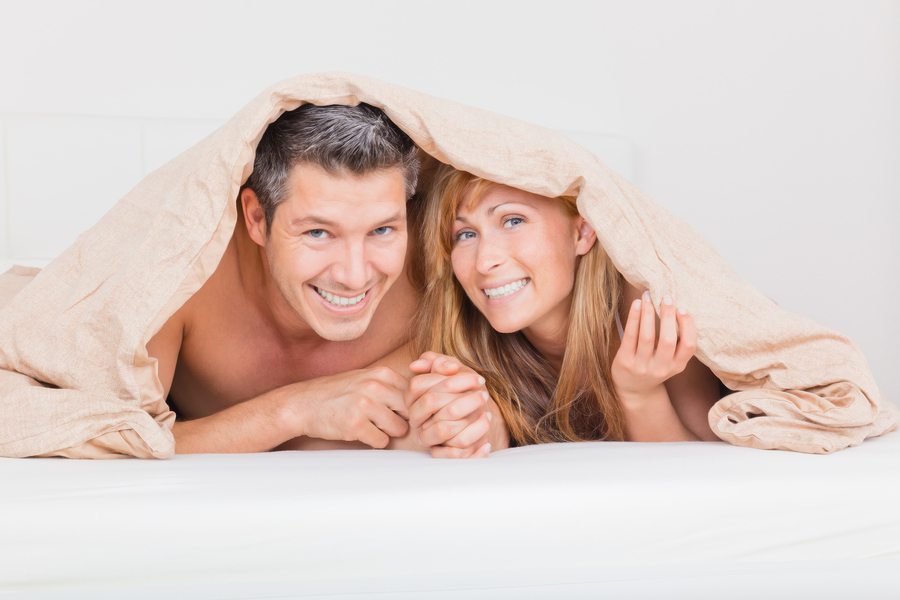 Couple peeking out from under a blanket.