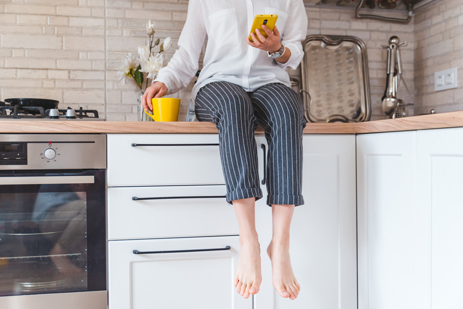 Woman sitting on her counter top with a cup of coffee and her phone.
