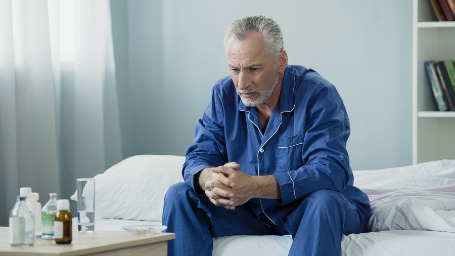 Man sitting at the side of his bed looking down.