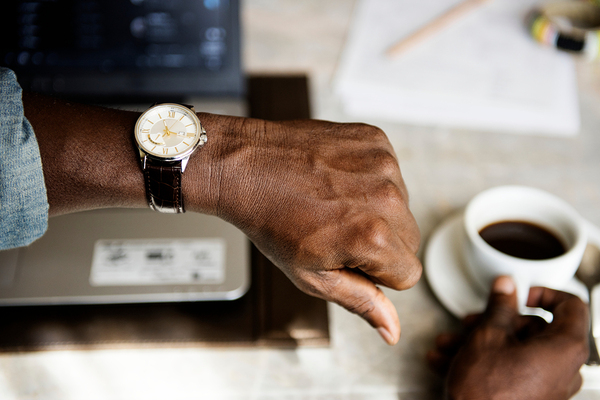 Man with coffee checking his watch
