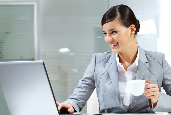 Happy woman working on a computer drinking coffee