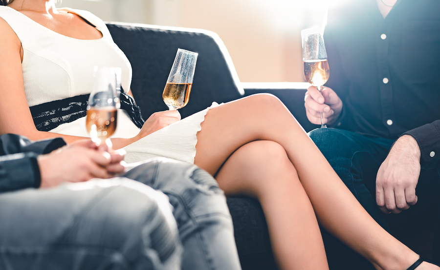 Group sitting on couches drinking champaign.