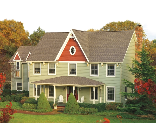 Green home and light grey shingled roof.