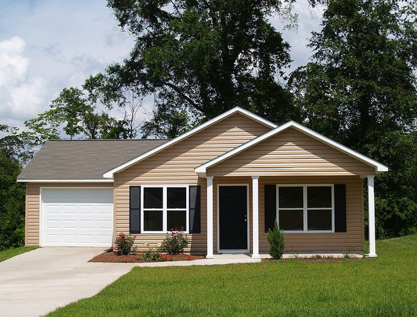 Tan colored home with white trim and single garage.