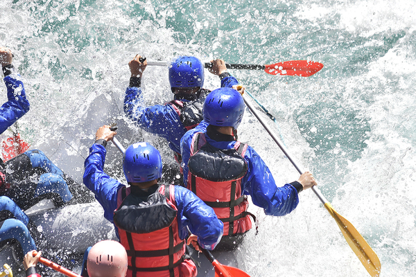 Group of people rafting down a river.