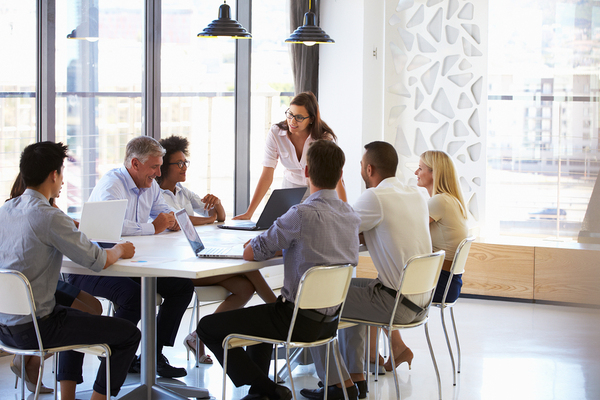 Group of people sitting around a conference table discussing ideas.