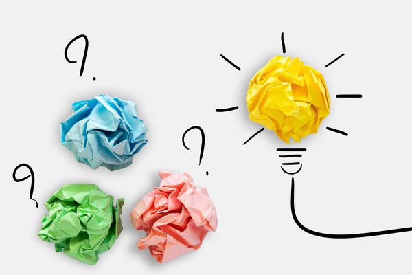 Crumpled up colored papers, and one yellow colored paper creating a lightbulb.