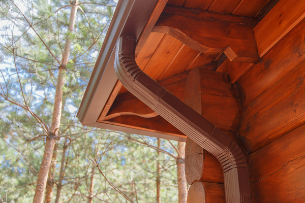 Brown gutters and downspout on a log cabin.