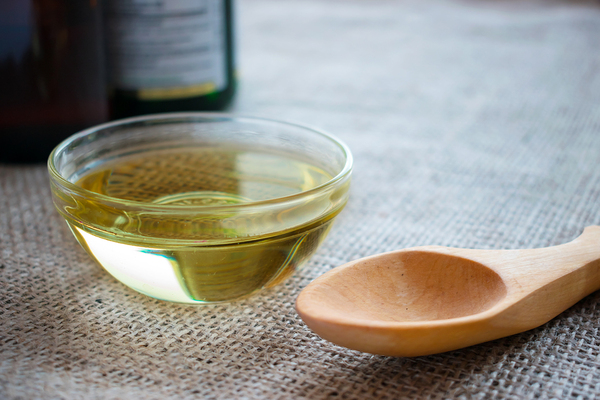 MCT oil in a small glass bowl with a wooden spoon nearby.
