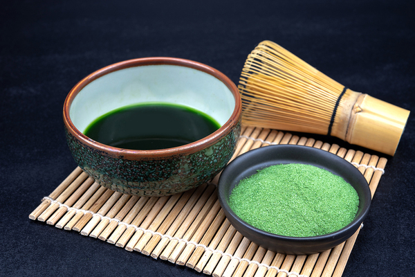 Placemat with a bowl of liquid and a bowl of green powder.