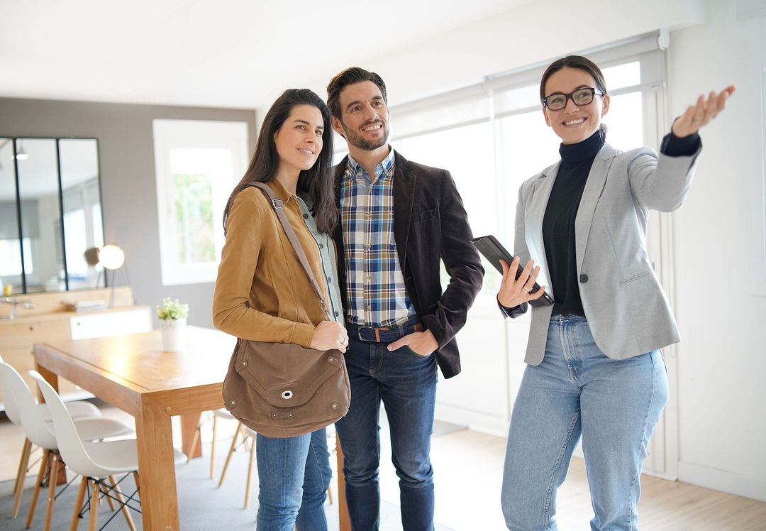 Couple looking at a new home with a real estate agent.