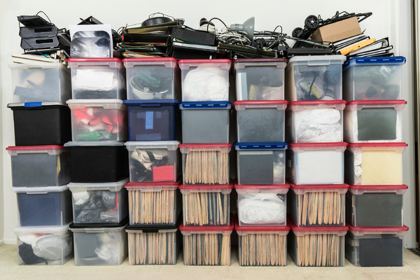 Multiple plastic storage boxes stacked with items.