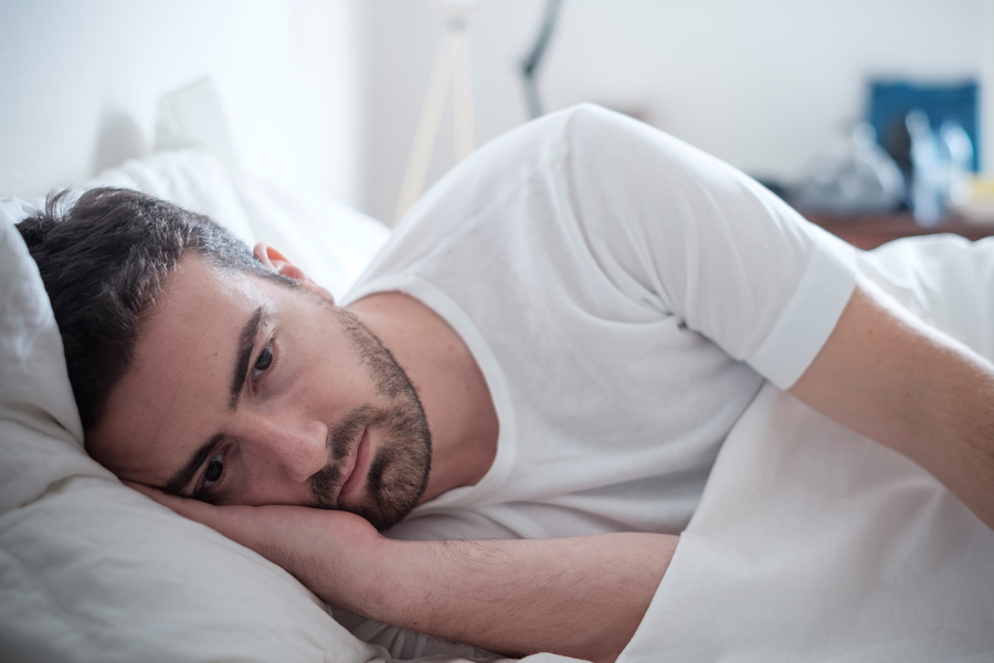 Man lying down appearing sad.