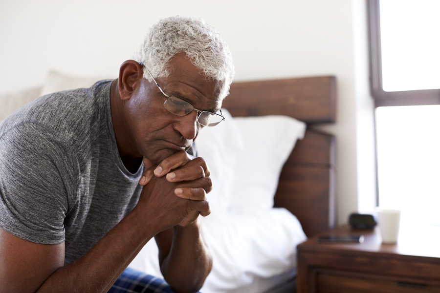 Man sitting at the edge of his bed.