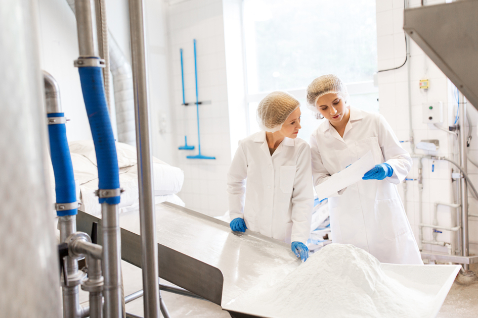 Two woman working with protective white jackets and hair nets.
