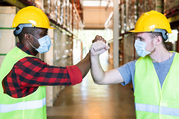 Two warehouse workers touching fists.