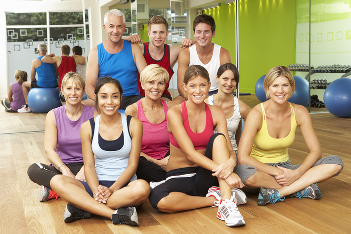 Group of people posing for a photo in a gym.