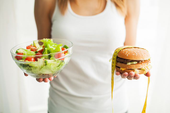 Woman holding a hamburger in one hand and a salad in the other.