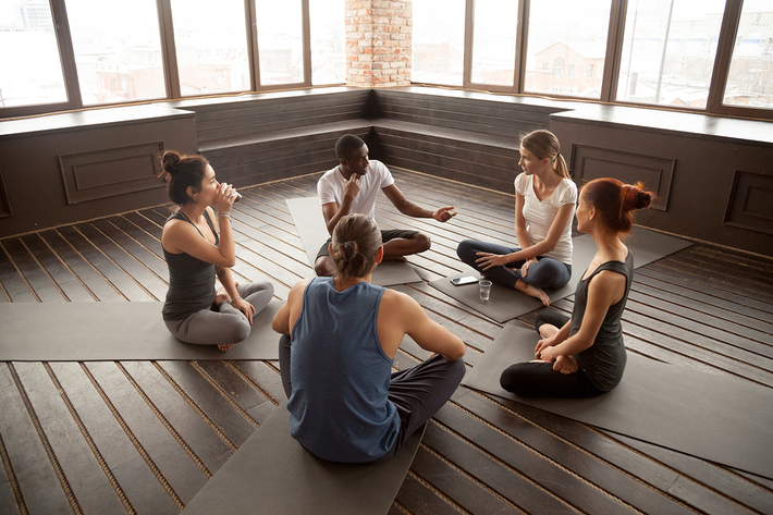 Five participants in a yoga class having a discussion.