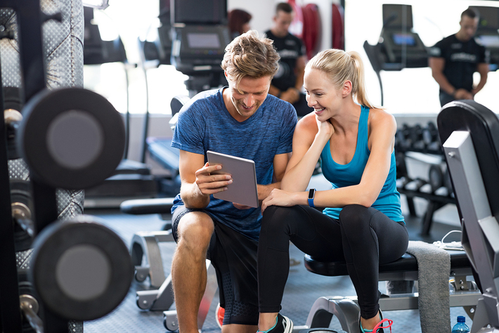 Woman and man in a fitness gym looking at a tablet together.