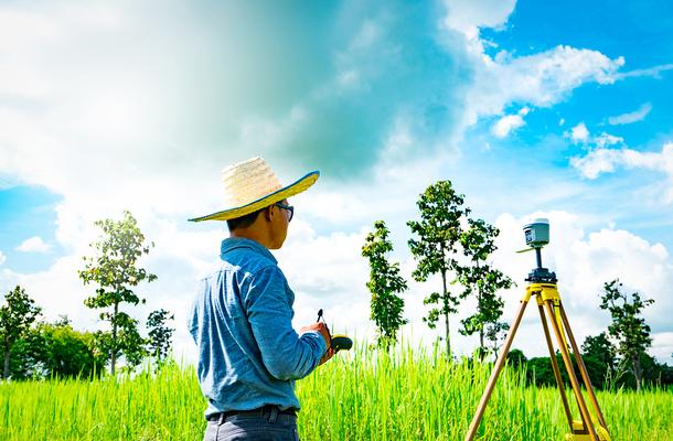 Land surveyor working in a grassy field.