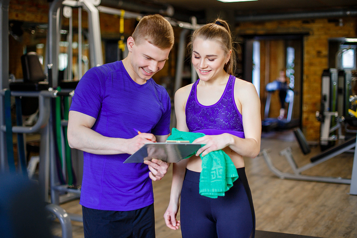 Woman consulting with a personal trainer in a gym.