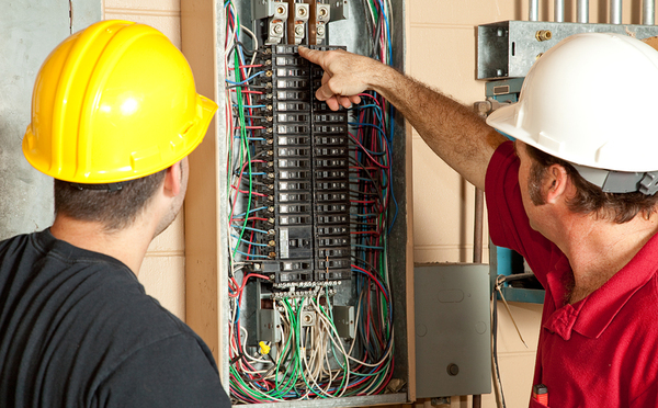 Two workers with hardhats looking at an electrical panel.